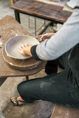 Crop artisan shaping clay plate with instrument