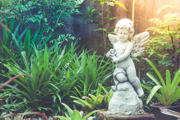 White cupid sculpture or statue standing in outdoor garden surrounded with green natural for decoration.