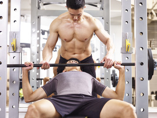 young asian man lifting weight in gym getting help from muscular trainer