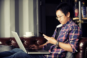 Business woman looking on mobile in hand at coffee shop, sitting on a sofa .