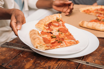 female hands holding plate with pizza
