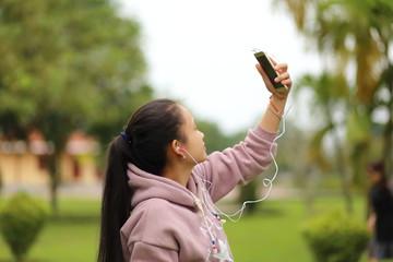 スマートホンで音楽を聴く女性