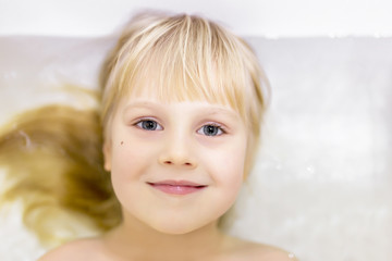 Portrait off cute little blond caucasian kid girl smiling  and  having fun while bathing