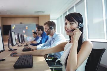 Portrait of happy businesswoman using headset
