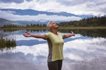 Senior woman with arms outstretched standing near the lake