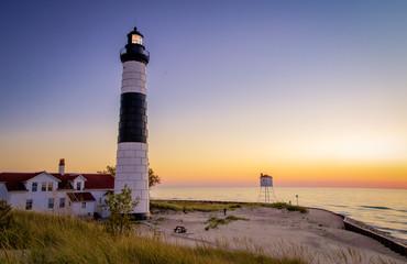 Michigan Lighthouse Coastal Sunset Background. Illuminated beacon of the Big Sable Lighthouse on the sandy coast of Lake Michigan at sunset. Ludington State Park in Ludington, Michigan.