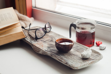 Still life details, book, glasses, cup of asian tea and teapot on vintage wooden tray on windowsill in living room. Lazy winter weekend with a book at home