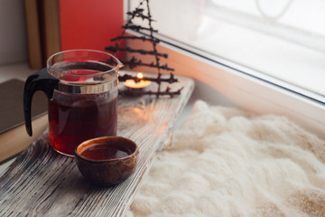 serving vintage tray witth cup of asian tea, teapot and candlestick on windowsill. comfy moody still life interior details
