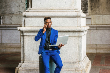 African American Businessman travels, works in New York. Wearing blue suit, black shirt, bow tie, man sits on metal pillar by column on street, works on laptop computer, talks on phone. Filtered look