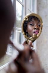 Dunkelhäutige Frau schminkt sich im Spiegel