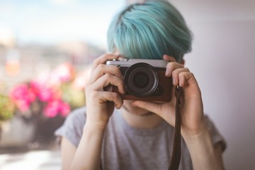 Woman taking picture from camera at home