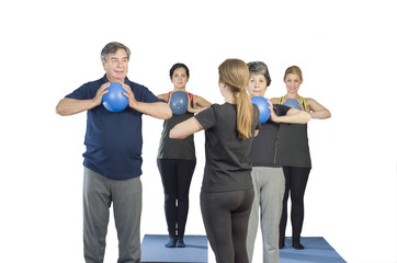 Diverse group of people a gym class doing ball Pilates exercise with a trainer over white background
