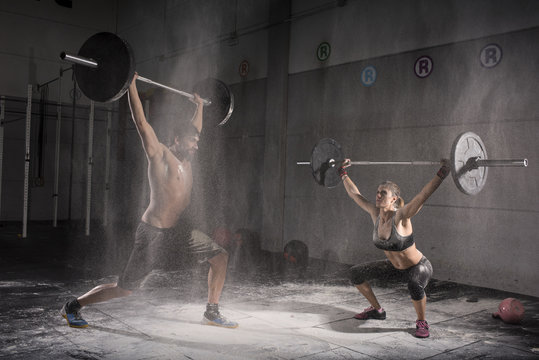 Motivational wide shot of young man and woman holding barbells overhead