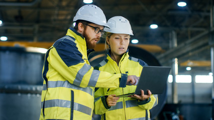 Male and Female Industrial Engineers in Hard Hats Discuss New Project while Using Laptop. They Make Showing Gestures.They Work at the Heavy Industry Manufacturing Factory.