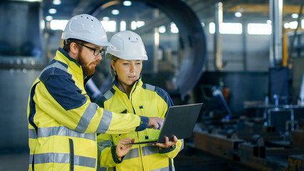 Male and Female Industrial Engineers in Hard Hats Discuss New Project while Using Laptop. They Make Showing Gestures.They Work in a Heavy Industry Manufacturing Factory. Wall mural