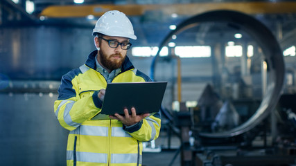 Industrial Engineer in Hard Hat Wearing Safety Jacket Uses Laptop. He Works in the Heavy Industry Manufacturing Factory with Various Metalworking Processes are in Progress. Wall mural