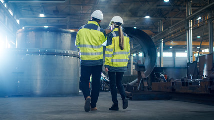 Male and Female Industrial Engineers use Laptop and Have Discussion While Walking Through Heavy Industry Manufacturing Factory. They Wear Hard Hats and Safety Jackets.