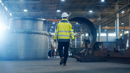Industrial Engineer in Hard Hat Wearing Safety Jacket Walks Through Heavy Industry Manufacturing Factory with Various Metalworking Processes. Wall mural