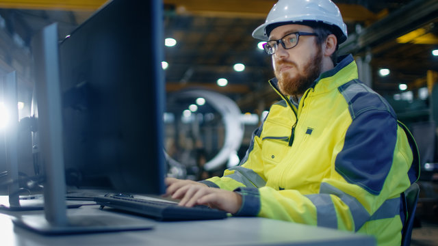Industrial Engineer Works at Workspace on a Personal Computer.  He Wears Hard Hat and Safety Jacket and Works in the Main Workshop of the Heavy Industry Manufacturing Factory.