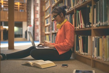 Girl using laptop in library