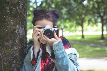 Girl photographing with vintage camera in park