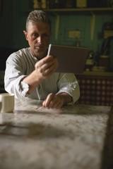 Senior man using digital tablet in kitchen