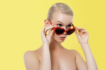 Valentine's Day concept. 14 february. Fashion Model girl isolated over yellow background. Beauty stylish blonde woman posing in heart shaped sunglasses. Casual style with beauty accessories