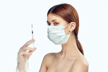 Young beautiful woman on white isolated background in medical mask holds syringe, portret, medicine, plastic surgery