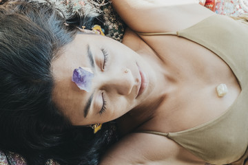 Woman laying down with crystals