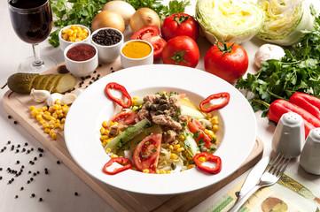 Fresh salad with chicken breast, arugula and tomato.