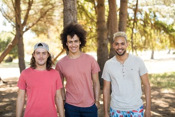 Portrait of smiling male friends at forest