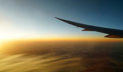 golden sunlight spreading on aerial cloud below airplane wing