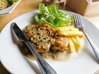 Chicken steak on wood table in restaurant with Black pepper sauce and salad.