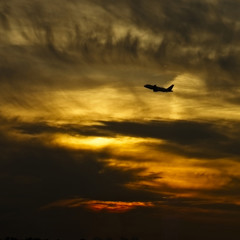 Silhouette of a jet airliner taking off at sunset, Germany.