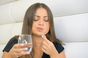 Sick young woman holding pill glass of water at work,depressed unhealthy woman, about to take antidepressant pill, emergency contraceptive, painkiller for painful periods.