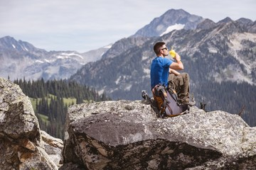 Male hiker sitting on rock and drinking water