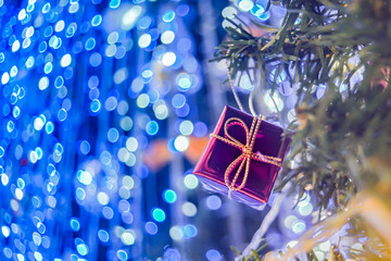 Pink gift box tied with gold rope ,hang on the fake pine Christmas tree. The background is blue.
