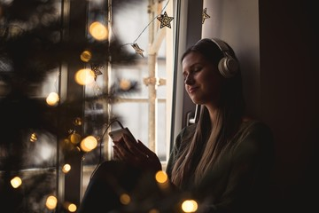 Woman listening to music on mobile phone during christmas eve