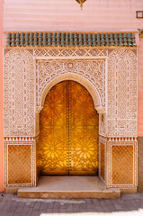 A gold metal door surrounded by intricate carved plaster in Marrakech, Morocco