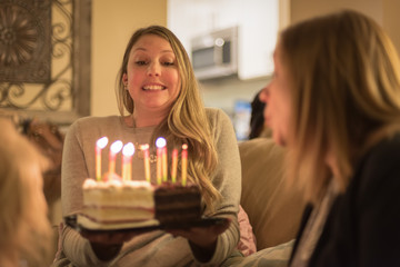 young woman holding birthday cake with glowng candles