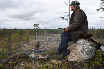 Moosehunter sitting on a stone with a fire in front of him