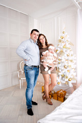 Baby girl wearing cute dress and headband with mother and father, near christmas tree in festively decorated room with garland of lights.