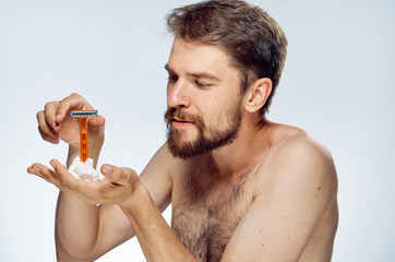 A man with a beard holds a machine and shaving foam on a light background