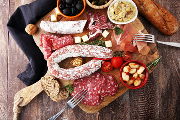 Italian antipasti wine snacks variety set. Cheese, Mediterranean olives, pickles, Prosciutto di Parma, tomatoes, artichokes and wine in glasses. Spanish tapas.