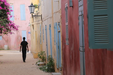 Silhouette of a lonely man walking in a narrow colored street of goree island in senegal