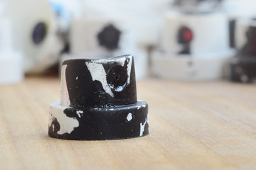 Several plastic nozzles from a paint sprayer that lie on a wooden surface against a gray wall background. The caps are smeared in black paint. The concept of street art and graffiti