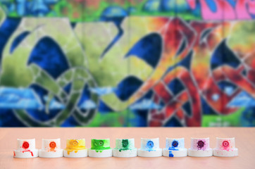 The soiled multicolored nozzles from the paint sprayer are lined up on a wooden table on a background of colored graffiti drawing in a wild style. The concept of street art