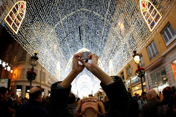A woman uses a mobile phone to take pictures of Christmas lights during a show of lights and songs to mark the start of the Christmas season in downtown Malaga
