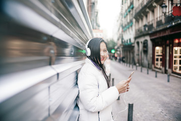 Asian woman with mobile phone and headphones.
