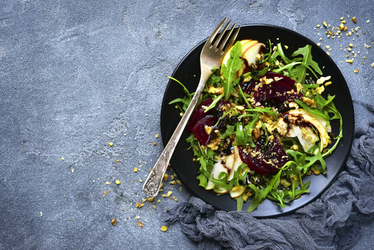 Vegetable salad with beetroot,apple,walnut and arugula leaves.Top view.